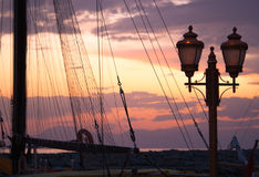 View of the mast of a ship with gear and street light. View of the mast of a ship with gear and street light on the background of the sunset Stock Photo