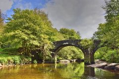 Picturesque Old Bridge of South West England. View in May of the picturesque old Hexworthy or Huccaby Bridge over the West Dart river, Dartmoor Forest, Devon royalty free stock photography