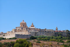 View of Mdina's St. Paul's Cathedral from the countryside below,. The view of the old capital Mdina surrounding by the fortress wall from the countryside below Royalty Free Stock Photography