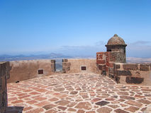 View from mediaeval fortress wall on hilltop. Mountains and volcanoes on deep blue horizon Royalty Free Stock Photo