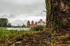 View of medieval castle in the Belorussian town of Mir through the tree against the somber sky. Mir, Belarus - September 05, 2016 Royalty Free Stock Image