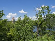 view on medieval czech castle Zvikov round tower and river Vltava, green trees in foreground blue sky, white clouds background royalty free stock images