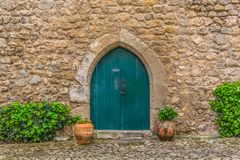 "View of the medieval gate door on Luso Roman castle of Ã""bidos, with ceramic pot with plants, in Portugal. Obidos / Leiria / Portugal - 04 04 2019 : View of stock photo"