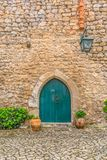 "View of the medieval gate door on Luso Roman castle of Ã""bidos, with ceramic pot with plants, in Portugal. Obidos / Leiria / Portugal - 04 04 2019 : View of stock images"