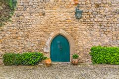 "View of the medieval gate door on Luso Roman castle of Ã""bidos, with ceramic pot with plants, in Portugal. Obidos / Leiria / Portugal - 04 04 2019 : View of stock photos"
