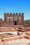 Castle tower and ruins, Silves, Portugal. View of the Medieval ruins inside the castle showing with the battlements and one of the towers to the rear, Silves Stock Photo