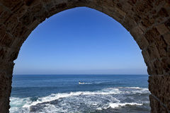 Arch View to the Sea. View at the Mediterranean sea with a fisherman's boat from within an arched window set in the fortified wall surrounding the old town of Stock Photos