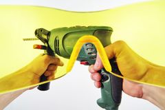 View of men`s hands with an electric drill through yellow protective glasses. First-person view. Strong men`s hands hold an electric drill. View through the Royalty Free Stock Photos