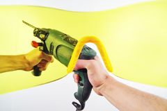 View of men`s hands with an electric drill through yellow protective glasses. First-person view. Strong men`s hands hold an electric drill. View through the Stock Image