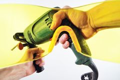 View of men`s hands with an electric drill through yellow protective glasses. First-person view. Strong men`s hands hold an electric drill. View through the Stock Photography