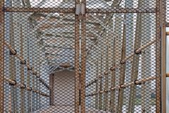 VIEW THROUGH MESH GATE. Locked metal gate restricting access to gangplank Royalty Free Stock Photos