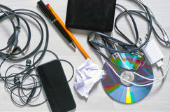 View of a messy tabletop. View of a messy wooden table with a cables, cd, charger, external hdd, earphones, pencil and pen on itr royalty free stock images