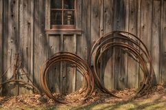 Wagon Wheel Rims Leaning on a Rustic Building Royalty Free Stock Photography
