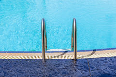 The view of metallic ladder entrance to clear blue swimming pool Stock Photography