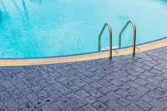 The view of metallic ladder entrance to clear blue swimming pool Royalty Free Stock Image