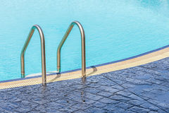The view of metallic ladder entrance to clear blue swimming pool Royalty Free Stock Photography