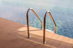 The view of metallic ladder entrance to clear blue swimming pool Stock Images