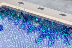The view of metallic ladder entrance to clear blue swimming pool Stock Image