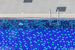 The view of metallic ladder entrance to clear blue swimming pool Stock Photos