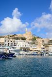View of Mgarr harbour, Gozo. Traditional fishing boats in the harbour with the Our Lady of Lourdes church on the hillside to the rear, Mgarr, Gozo, Malta Stock Photos