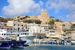 View of Mgarr harbour, Gozo. Traditional fishing boats in the harbour with the Our Lady of Lourdes church on the hillside to the rear, Mgarr, Gozo, Malta Royalty Free Stock Images