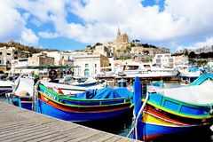 View of Mgarr town and harbour, Gozo. Traditional fishing boats in the harbour with the Our Lady of Lourdes church on the hillside to the rear, Mgarr, Gozo Stock Photography