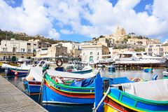 View of Mgarr town and harbour, Gozo. Traditional fishing boats in the harbour with the Our Lady of Lourdes church on the hillside to the rear, Mgarr, Gozo Royalty Free Stock Image