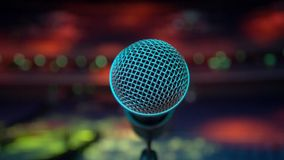 View of microphone on stage facing empty auditorium.  Colorful spotlights Royalty Free Stock Photo