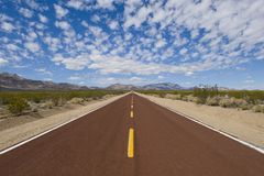 View from the middle of a straight road running through deserted land Royalty Free Stock Image