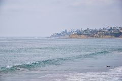 View from Mission Beach in San Diego, of Piers, Jetty and sand, around surfers, including warning signs, palm trees, waves, rocks,. Boats and horizon views royalty free stock images