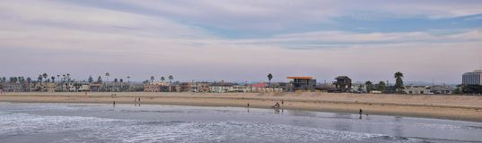 View from Mission Beach in San Diego, of Piers, Jetty and sand, around surfers, including warning signs, palm trees, waves, rocks,. Boats and horizon views stock photos