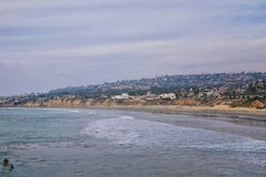 View from Mission Beach in San Diego, of Piers, Jetty and sand, around surfers, including warning signs, palm trees, waves, rocks,. Boats and horizon views stock photo