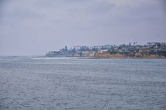 View from Mission Beach in San Diego, of Piers, Jetty and sand, around surfers, including warning signs, palm trees, waves, rocks,. Boats and horizon views stock photography