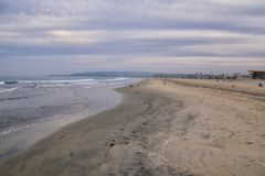 View from Mission Beach in San Diego, of Piers, Jetty and sand, around surfers, including warning signs, palm trees, waves, rocks,. Boats and horizon views royalty free stock photos