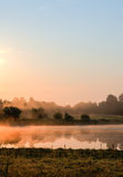 View of a misty bog. Mist, illuminated by the sun rising, drifts above a bog stock photo