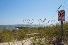 A view of Mobile Bay at Dauphin Island Alabama. Sea oats are waving in the breeze and waves are slowing rushing the shoreline at a rock lined jetty in Mobile Bay Royalty Free Stock Photography