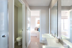 View of a modern bathroom with toilet and way to the bedroom. Closeup of a big mirrors on the wall near to the tap and white sink with liquid soap bottle, the Stock Photography