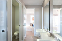 View of a modern bathroom with toilet and way to the bedroom. Closeup of a big mirrors on the wall near to the tap and white sink with liquid soap bottle, the Stock Image