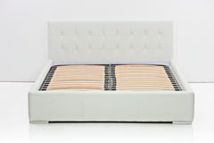A view of a modern bed. In an empty room Stock Photo