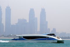 View of a modern ferry of Dubai water public transportation connecting several districts within Dubai. Business Bay in background. royalty free stock images