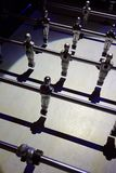 A view from a modern foosball, or bar foot, or table foot, with shining soccer or footballer miniatures Stock Photography
