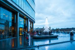 View of a modern glass Christmas tree standing next to the City. LONDON, UK - DECEMBER 16, 2017: A large contemporary LED Christmas tree decorates the riverside stock images