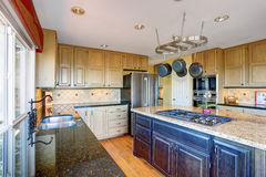 View of modern kitchen room interior with kitchen island and honey color cabinets. Royalty Free Stock Image