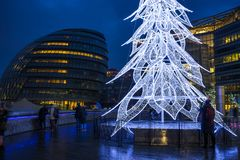 View of a modern LED Christmas tree standing next to the City H. LONDON, UK - DECEMBER 16, 2017: A large contemporary LED Christmas tree decorates the riverside stock images