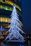 View of a modern LED Christmas tree standing next to the City H. LONDON, UK - DECEMBER 16, 2017: A large contemporary LED Christmas tree decorates the riverside stock image