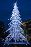 View of a modern LED Christmas tree standing next to the City H. LONDON, UK - DECEMBER 16, 2017: A large contemporary LED Christmas tree decorates the riverside stock photo