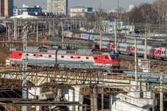 Moscow, Russia - April, 2017. View on modern Russian railway locomotive. View on modern Russian railway locomotive on a bridge above passenger trains stock image