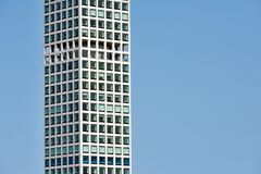 View of modern skyscraper against blue sky. View of modern skyscraper in business district area against blue sky Royalty Free Stock Photos