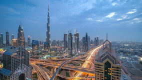 View on modern skyscrapers and busy evening highways day to night timelapse in luxury Dubai city, Dubai, United Arab