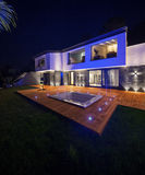 View of modern villa with pool in the night. Exteriors of modern luxury villa in the night stock photography